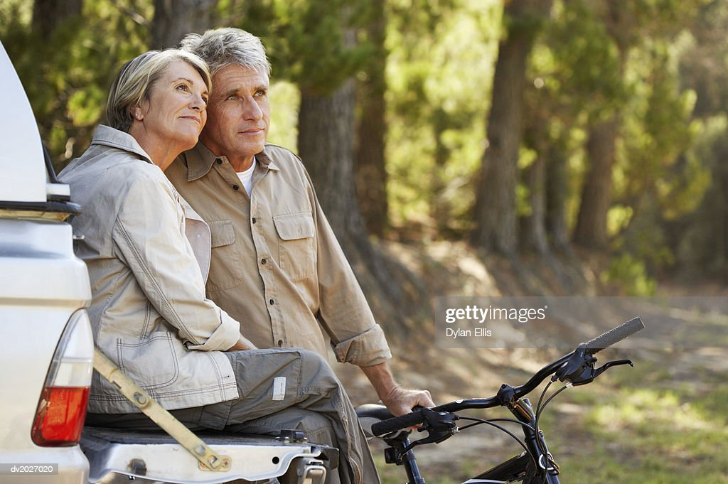 Senior Couple With Their Bikes at the Back of an SUV in Woodland : Stock Photo