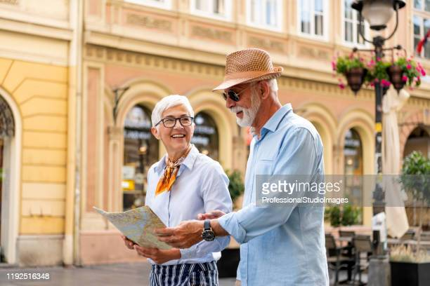 senior couple with tourist map is exploring the city - studio city stock pictures, royalty-free photos & images
