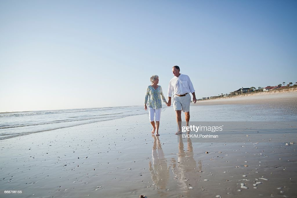 Senior couple with walking on beach holding hands : Stock Photo