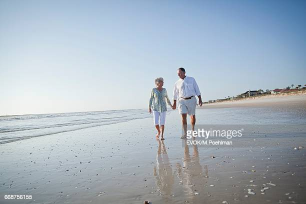 senior couple with walking on beach holding hands - jacksonville florida stock pictures, royalty-free photos & images