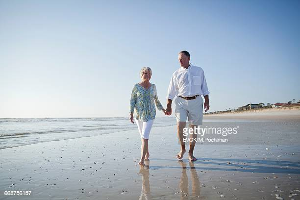 Senior couple with walking on beach holding hands