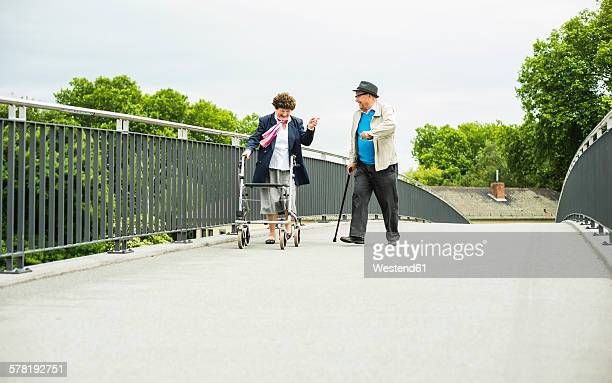 Senior couple with walking stick and wheeled walker on a bridge
