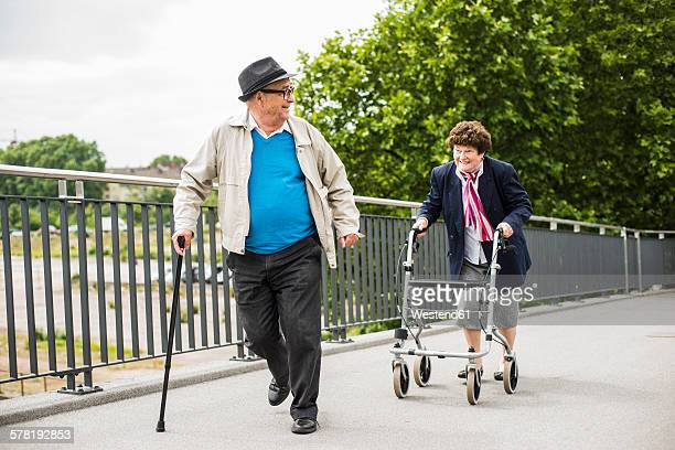 Senior couple with walking stick and wheeled walker