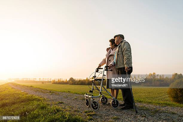 Senior couple with walking stick and wheeled walker standing in the nature