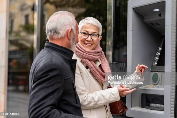 seniorencoupple-auszahlungsgeld aus einem geldautomaten - geldautomat stock-fotos und bilder