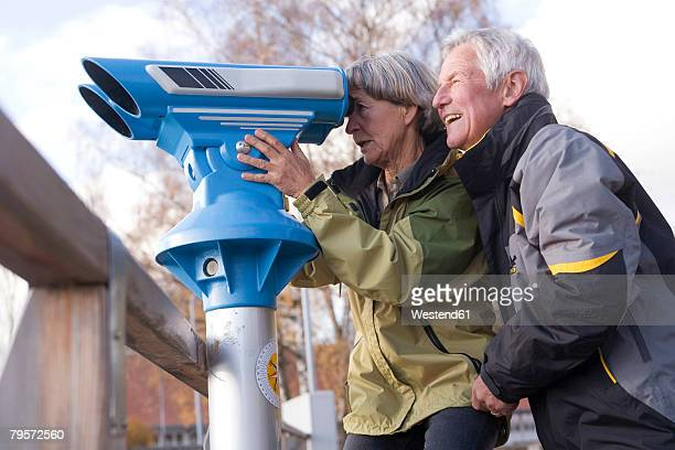 'Senior couple, woman looking through telescope, side view'