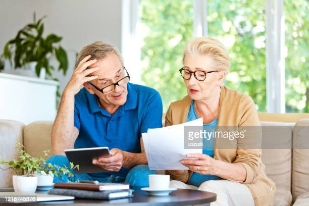 senior couple working out a home budget - negative emotion stock pictures, royalty-free photos & images