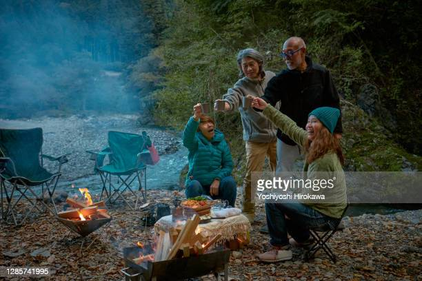 senior couples barbecuing at riverside campsite with sustainability - キャンプする ストックフォトと画像