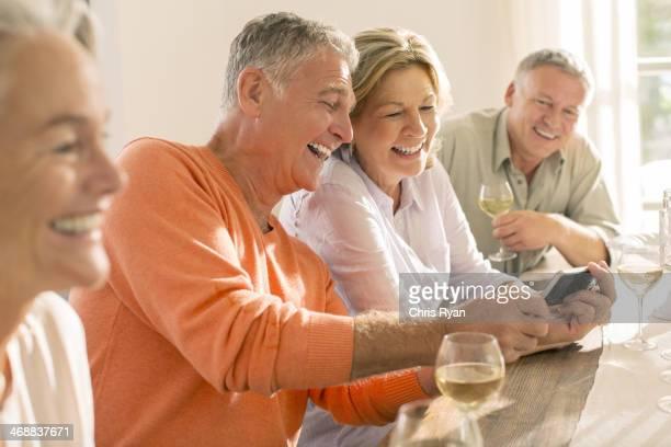 Senior Paare trinkt Wein und Blick auf Handy