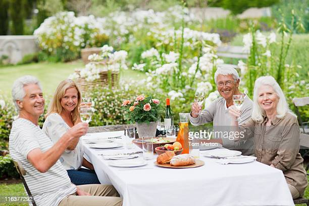 Senior couples drinking wine at table in garden