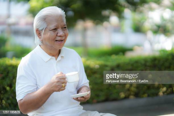 "senior couples happily sit and drink coffee in the morning at the park. - ""panyawat boontanom"" stockfoto's en -beelden"