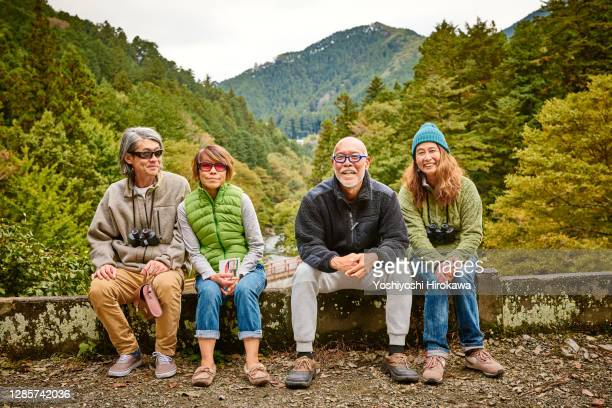 senior couples hiking along trail in forest on sunshine morning - japan stock pictures, royalty-free photos & images