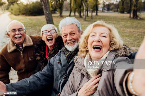 senior couples laughing on a bench in a park - senior adult stock pictures, royalty-free photos & images