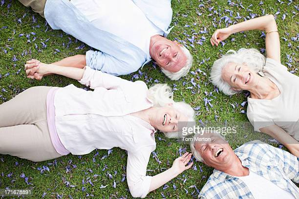 Senior couples laying on grass