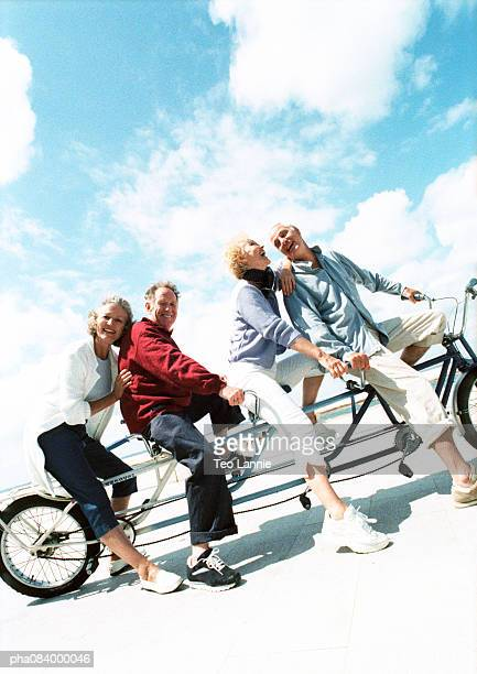 senior couples on tandem bike at beach, portrait. - tandem bicycle stock pictures, royalty-free photos & images