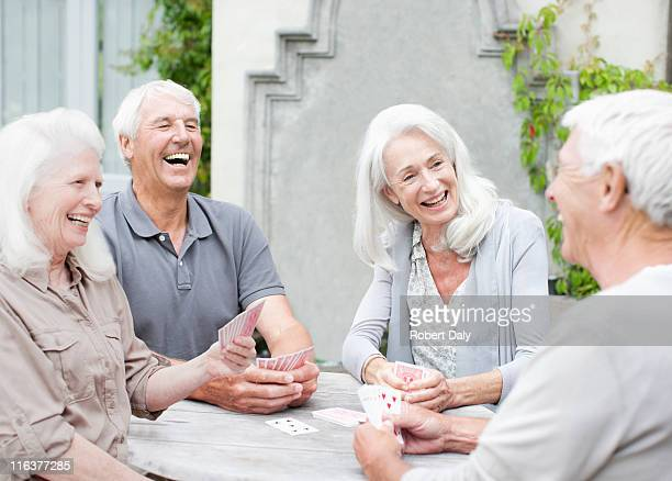 Senior couples playing cards on patio