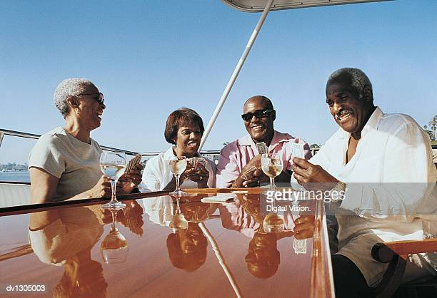 Senior Couples Playing Cards on the Deck of a Boat
