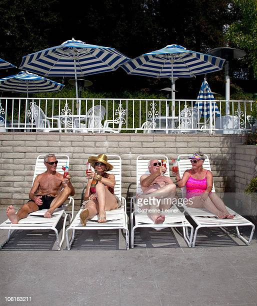 senior couples sunbathing and enjoying drinks. - old man in speedo stock photos and pictures