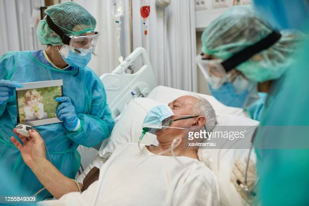 senior covid-19 patient on video call with granddaughter - frontline worker stock pictures, royalty-free photos & images