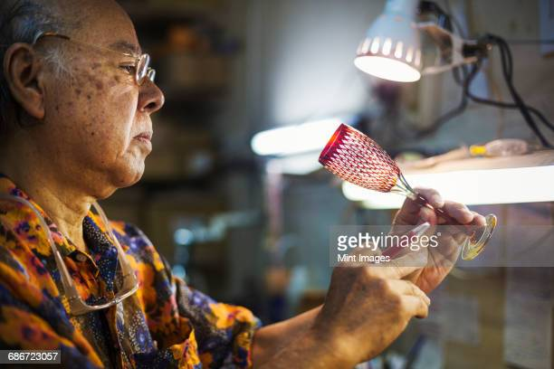 A senior craftsman at work in a glass makers studio workshop, in inspecting red wine glass with cut glass decoration against the light.