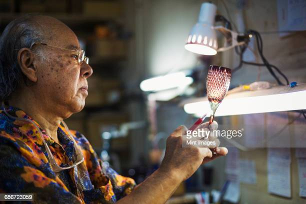 a senior craftsman at work in a glass makers studio workshop, in inspecting red wine glass with cut glass decoration against the light.  - craft product stock pictures, royalty-free photos & images