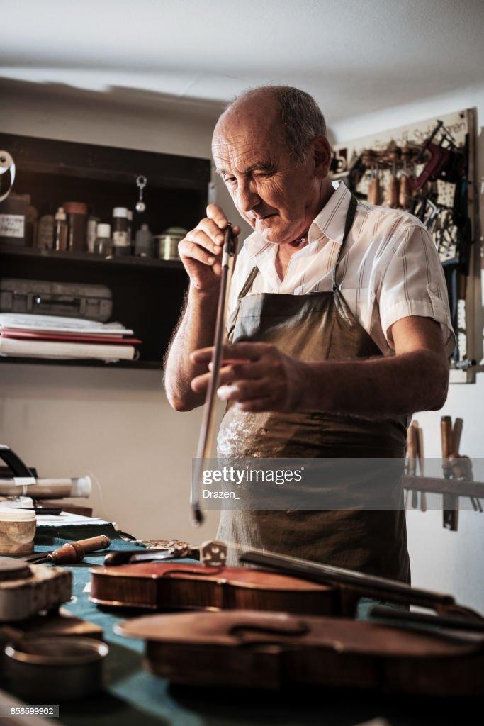 Senior Handwerker Überprüfung Saiten der Violine : Stock-Foto