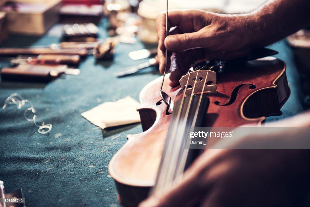 Senior craftsman checking the violin in his workshop : Stock Photo