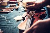 Senior ambachtsman controleren de viool in zijn atelier