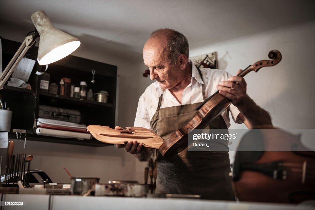 Senior Handwerker Violine Körper zu öffnen, um das Instrument zu überprüfen : Stock-Foto