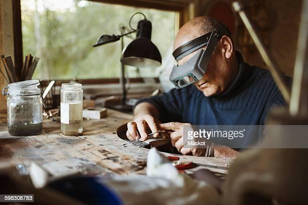 Senior craftsman working at table in workshop