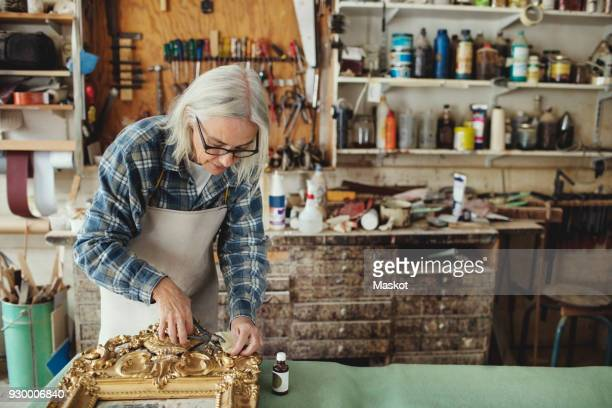 senior craftsperson working over carved wooden frame at table in workshop - active seniors stock pictures, royalty-free photos & images