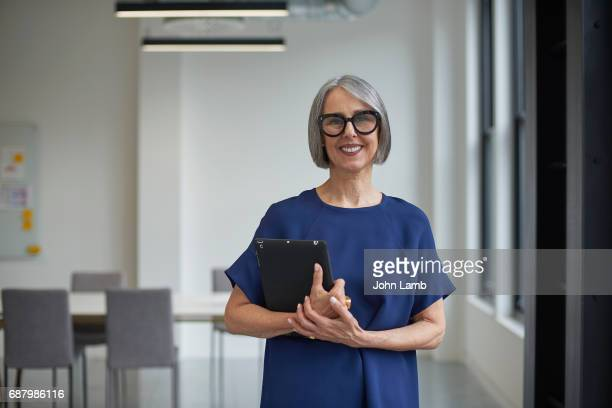 senior creative businesswoman with tablet computer - leanincollection stock pictures, royalty-free photos & images