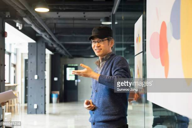 senior creative professional giving a presentation at conference - koreanischer abstammung stock-fotos und bilder