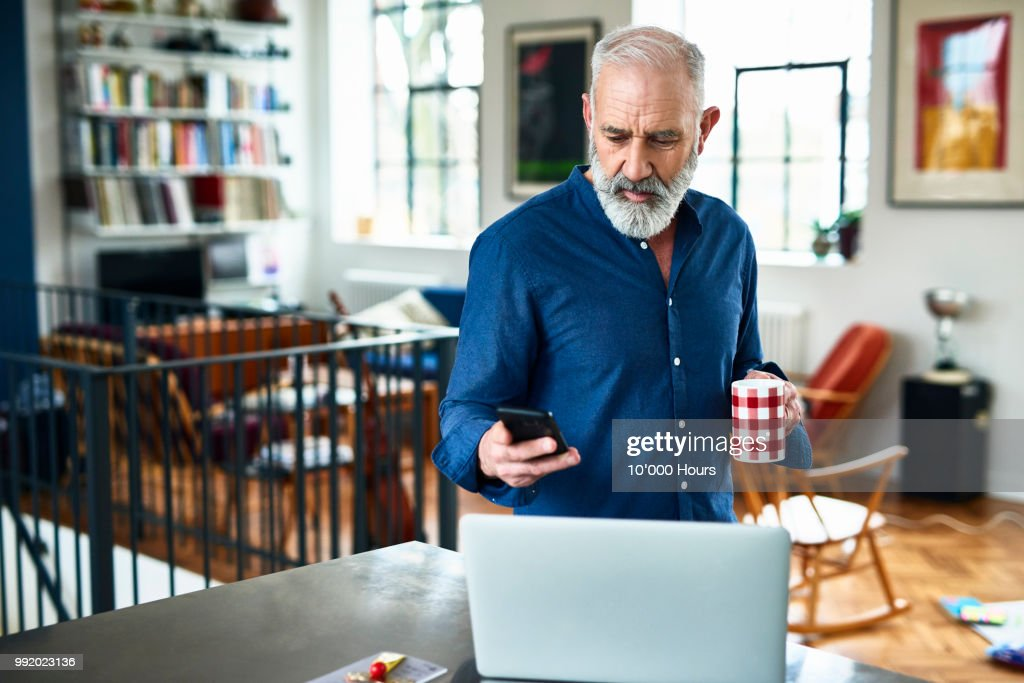 Senior creative professional remote working and checking phone at home : Foto de stock