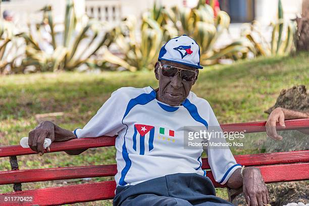 Senior Cuban Afro Caribbean man sitting in a bench wearing the Cuban flag and the Toronto Blue Jays cap Sports are very popular and a main theme of...