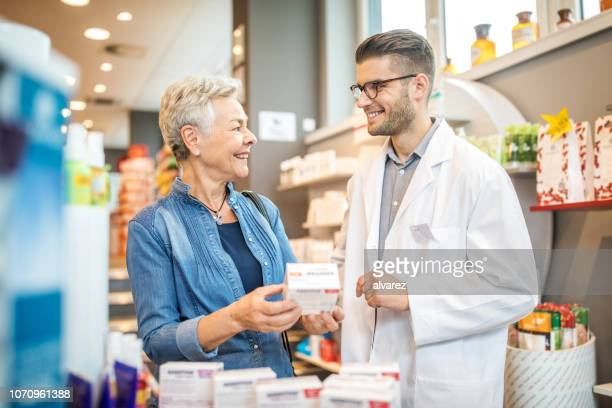 senior customer consulting medicine with pharmacist - pharmacy stock pictures, royalty-free photos & images