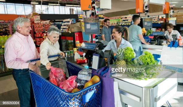 Älteren Kunden kaufen ihre Lebensmittel in einem Supermarkt und freundliche Verkäuferin, die ihnen helfen, mit der Kasse