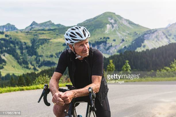 senior cyclist in the french alps - travel stock pictures, royalty-free photos & images