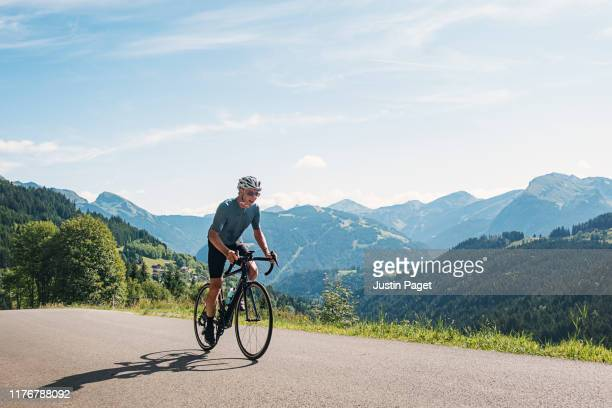 senior cyclist on the col de l'encrenaz - racing bicycle stock pictures, royalty-free photos & images