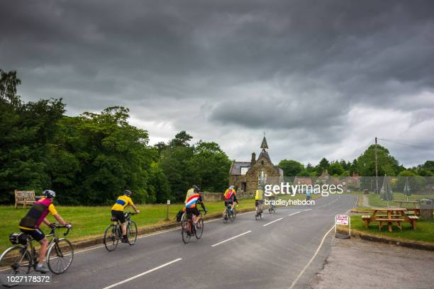 Senior cyclists make their way through the charming village of Hutton-Le-Hole in North Yorkshire
