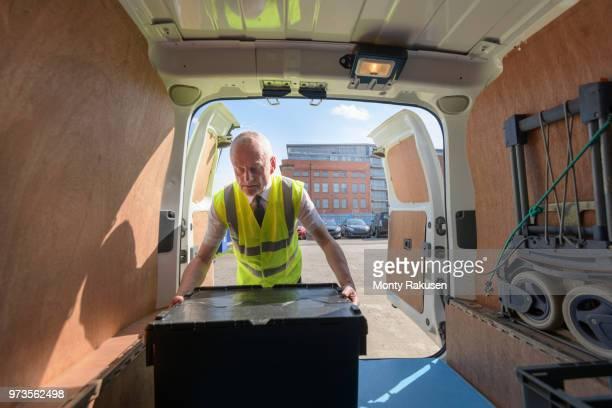 senior delivery driver loading all electric van - monty shadow - fotografias e filmes do acervo