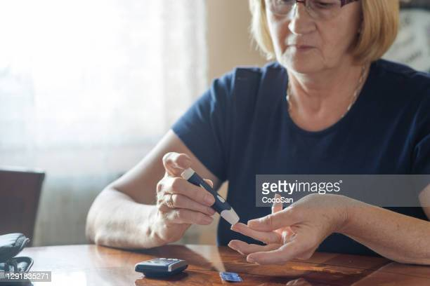 senior diabetic checking blood and glucose level after lunch - finger stock pictures, royalty-free photos & images