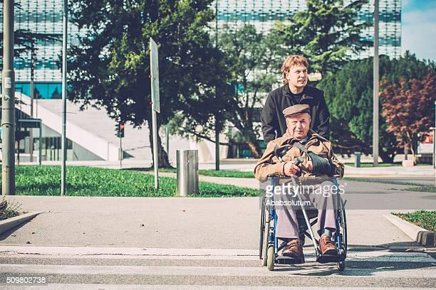 Sênior homem com deficiência em cadeira de rodas e neto ao ar livre, a Europa