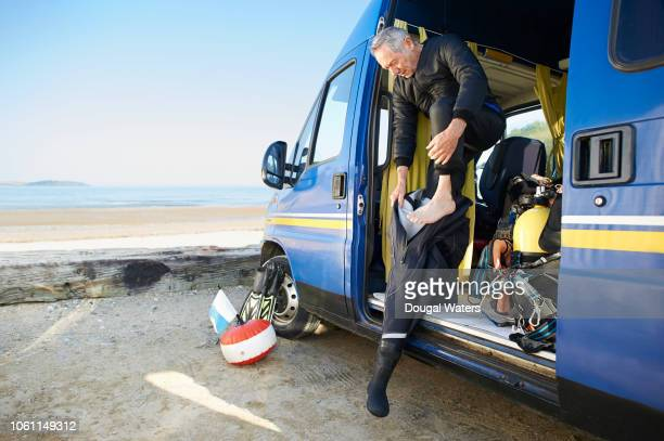 senior diver getting into wetsuit. - dougal waters stock pictures, royalty-free photos & images