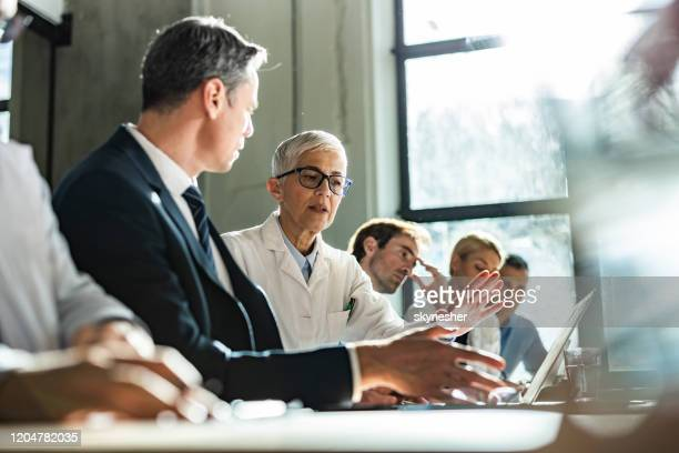 senior doctor and businessman using computer on a meeting with their colleagues. - administrator stock pictures, royalty-free photos & images