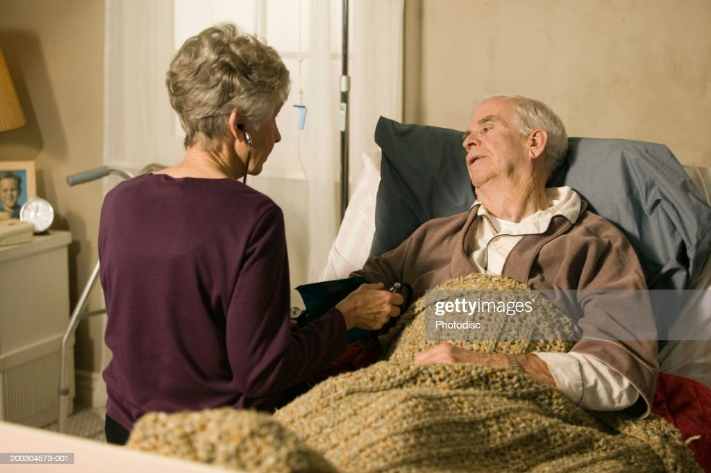 Senior doctor checking blood pressure of senior man in bed in retirement home : Stock Photo
