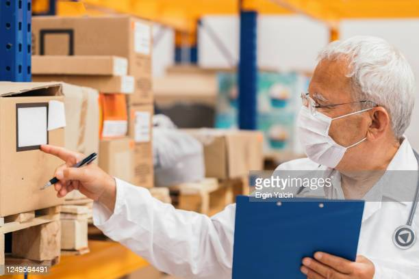 senior doctor checking medical stock in a warehouse - medical supplies stock pictures, royalty-free photos & images