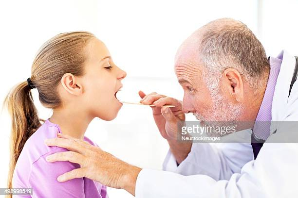 Senior Doctor Examining Girl's Mouth With Tongue Depressor