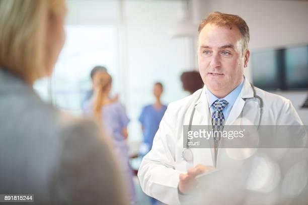 管理者に説明する先輩医師