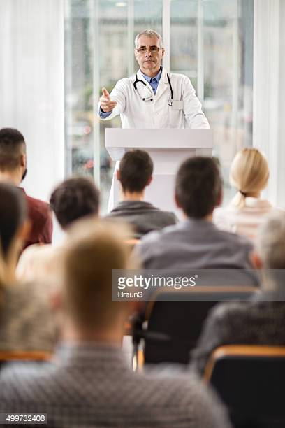 Senior doctor giving a speech on education event.
